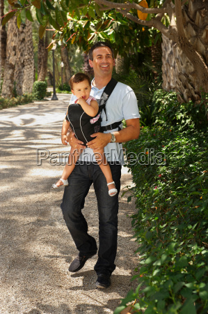 father carrying baby in park