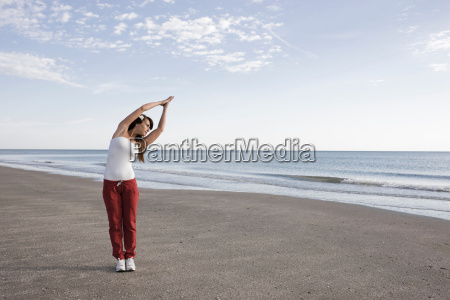 woman stretching on the shore