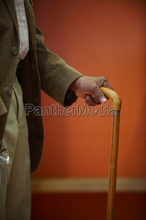 elderly mans hand on walking stick