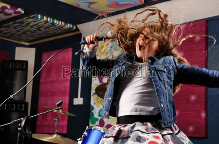 girl singing and jumping in studio