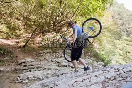 man crossing a stream with bike