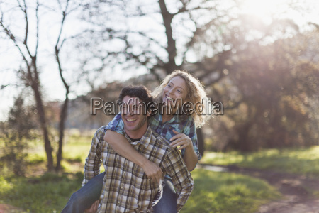man carrying girlfriend piggyback