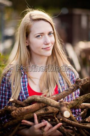 woman gathering firewood in garden