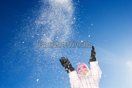 young girl throwing snow in the