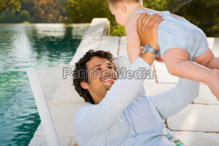 man holding up a baby by