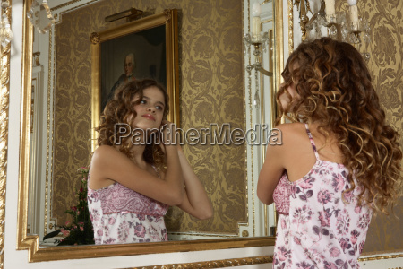 girl adjusing hair in mirror