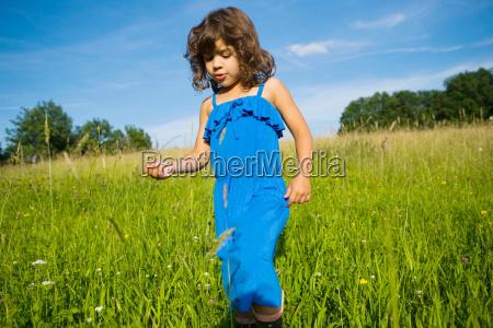 a girl walking through a field