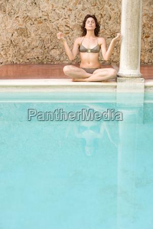 woman meditating by swimming pool