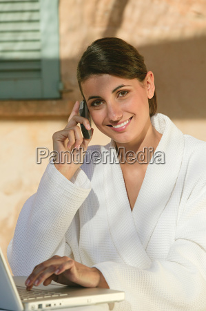 woman in bathrobe with cellphone and