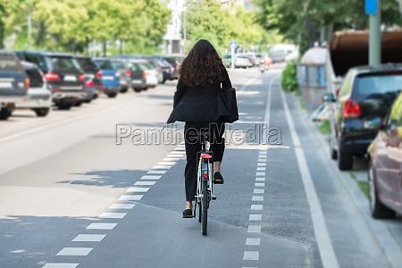 giovane imprenditrice in bicicletta in bicicletta