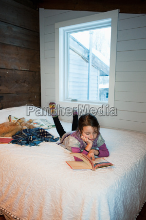 young girl lying on bed reading