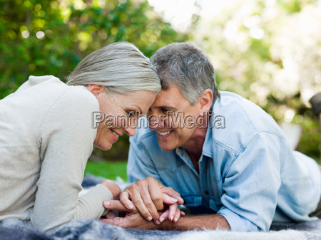 couple lying on picnic blanket in