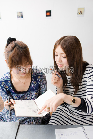young women looking at note book