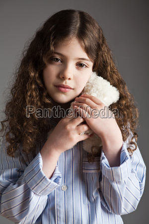 young girl dressed in pyjamas holding