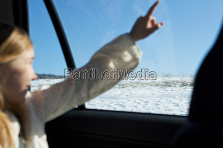 young girl pointing through car window