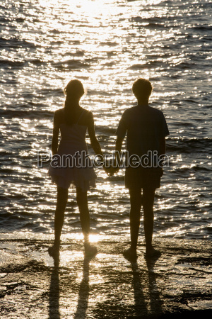 teenage couple watching sunset over sea