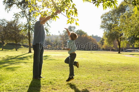 boy jumping to reach tree branch
