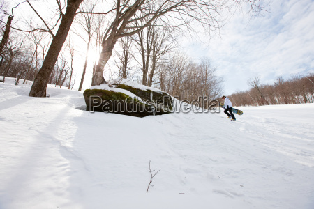 young man walking uphill with snowboard
