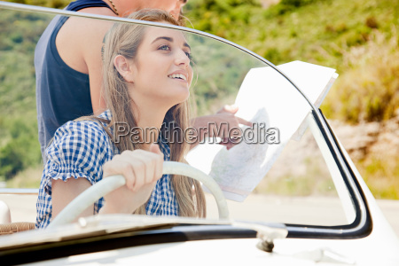 young people with convertible car looking