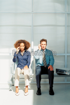 businessman and businesswoman talking on cellphones