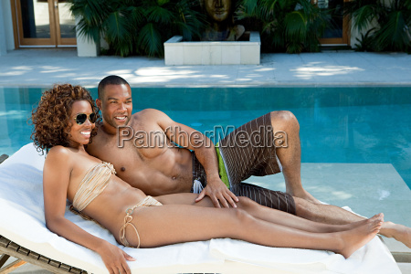 couple lying on sun lounger by