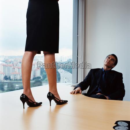 businessman watching woman on desk