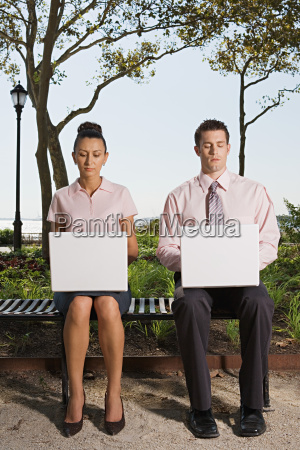 two people telecommuting in a park