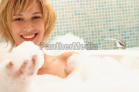 smiling young woman in bubble bath