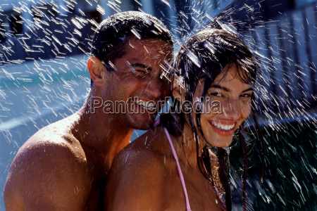 couple playing with water in garden