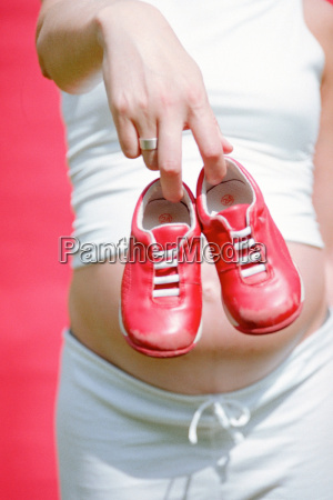 mother to be holding childs trainers