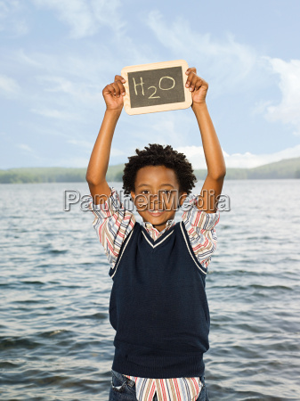 a boy holding a blackboard with