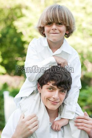 young boy on shoulders of older