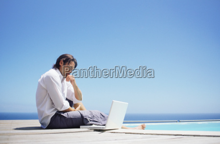 man with laptop by swimming pool