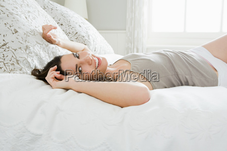 young woman lying on bed