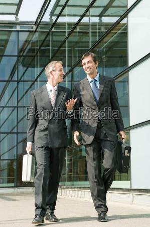 two businessman walking alongside office building