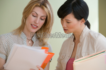 two young women looking at files