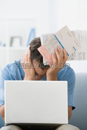 man with bills and a laptop