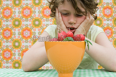 girl looking at bowl of radishes