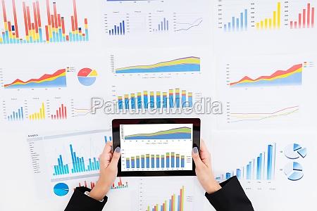 imprenditrice analizzando grafici finanziari con tavoletta