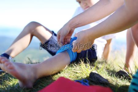 madre fornisce ai bambini ginocchio bendaggio