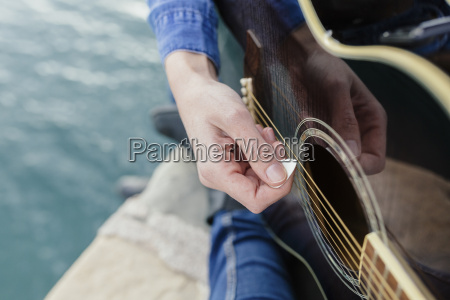 young woman at the waterfront playing