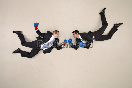 two flying businessmen boxing