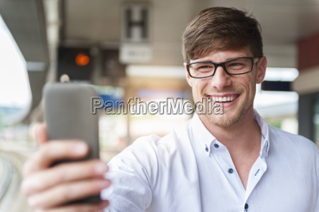 smiling young man at station platform
