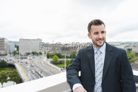 smiling businessman on roof terrace above