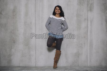 indiana femminile appoggiata a parete di