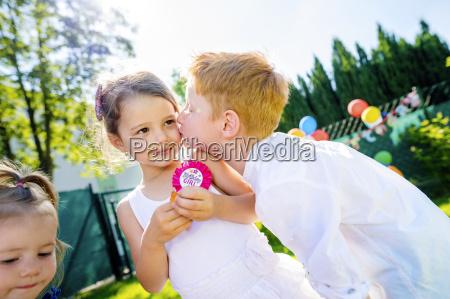 little boy kissing little girl at