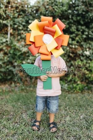 boy holding home made cardboard flower
