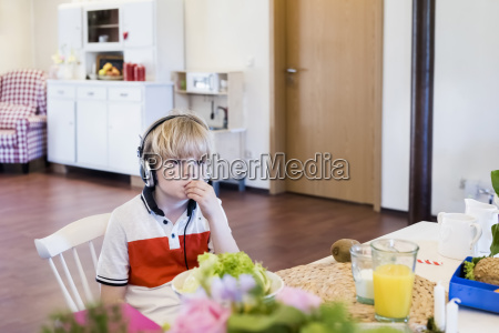 boy wearing headphones sitting at table