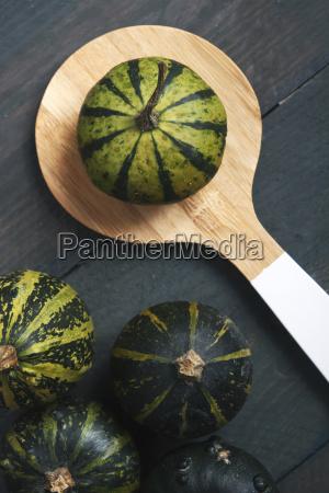 zucche ornamentali e cucchiaio di legno