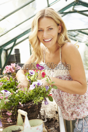 donna che coltiva piante in serra